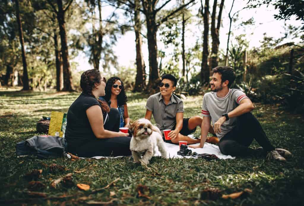A group of people sitting on the grass with a dog